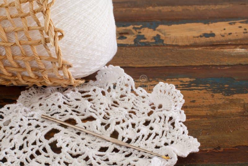在木桌上的钩针编织小垫布。选择聚焦 库存照片