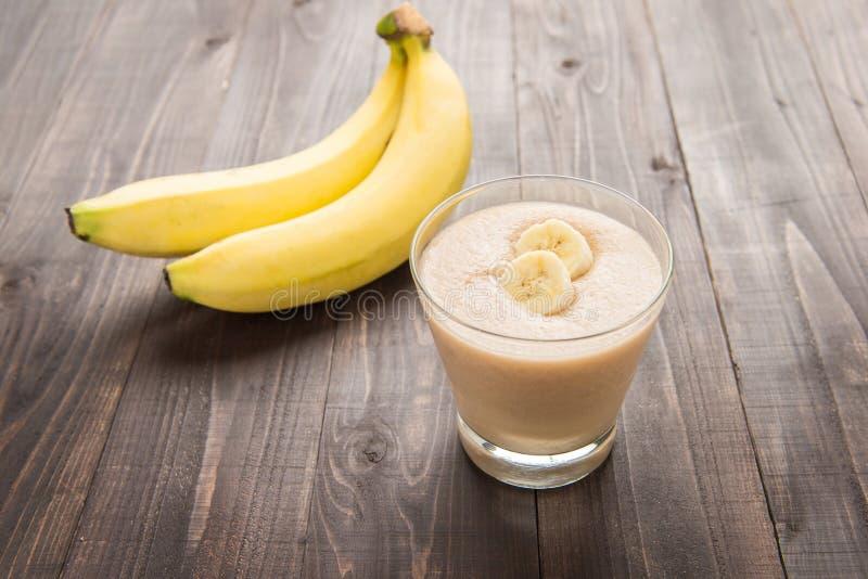 在木桌上的香蕉圆滑的人 图库摄影