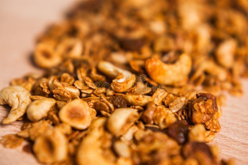 在木桌上的鲜美溢出的自创格兰诺拉麦片 库存图片
