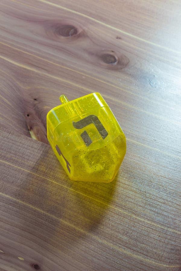在木桌上的黄色透亮塑料光明节dreidel,面对西伯来的信件嘿  免版税库存图片