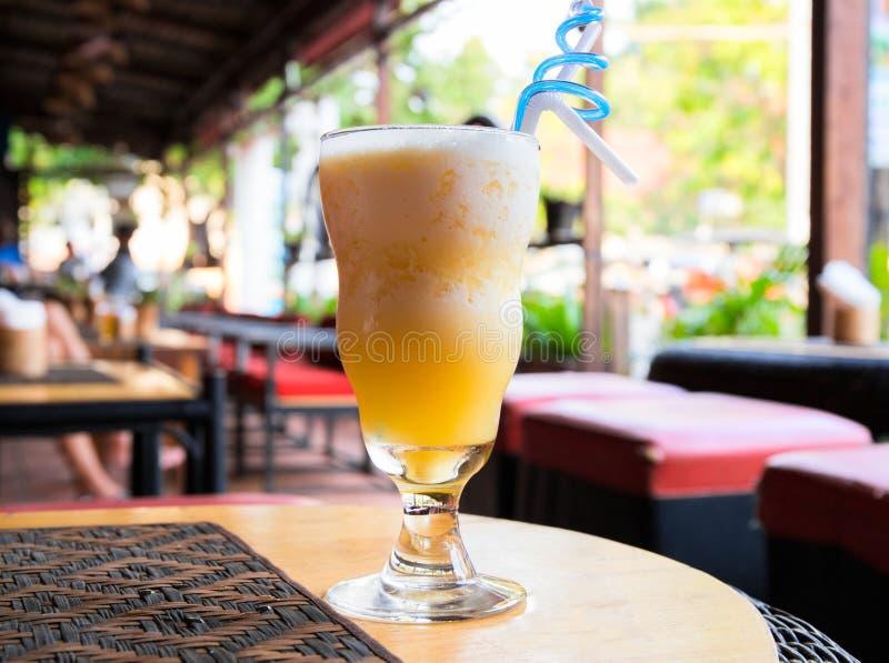 在木桌上的黄色鸡尾酒 为饮料服务的黄色芒果震动 热的天刷新的饮料 库存照片