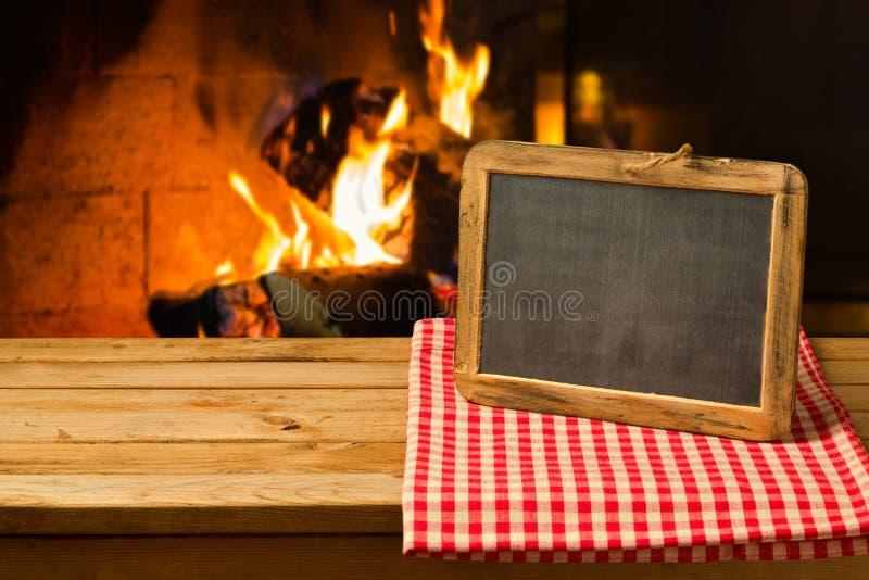 在木桌上的黑板在壁炉背景 冬天和圣诞节假日 图库摄影