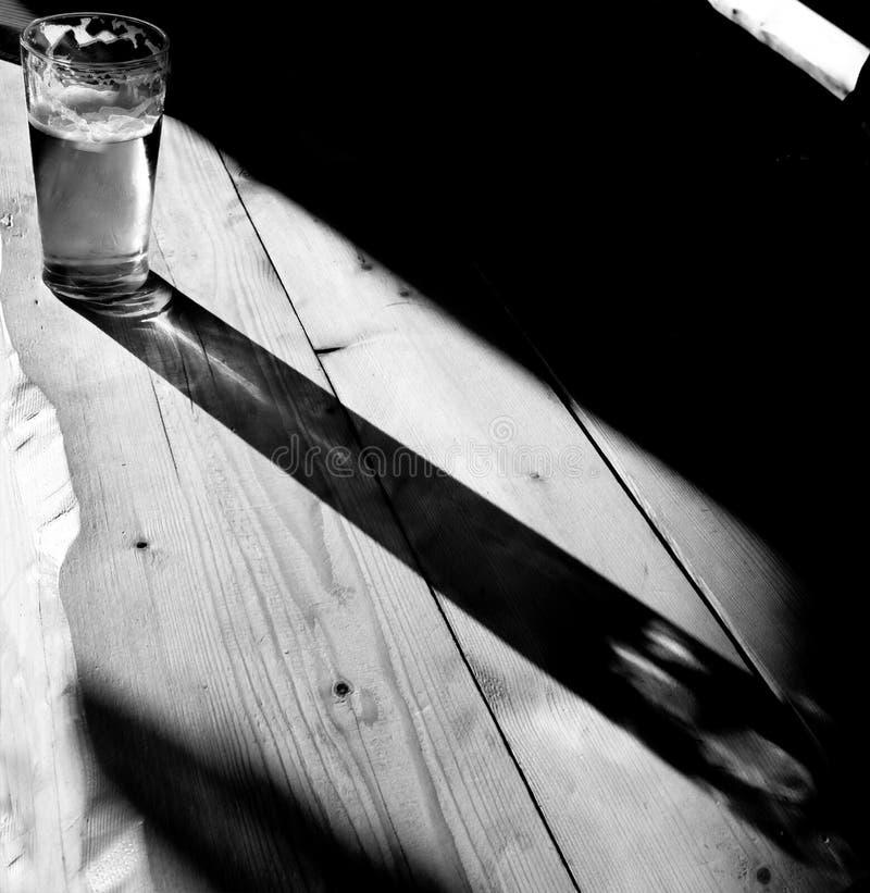 在木桌光和阴影比赛的啤酒杯:黑白 库存照片
