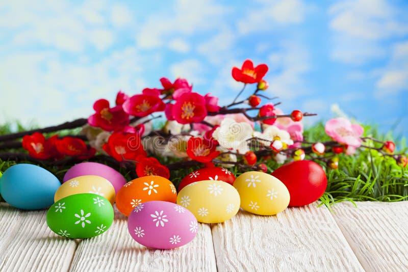 在木桌和分支上的五颜六色的复活节彩蛋与在草和天空蔚蓝背景的花 免版税库存照片