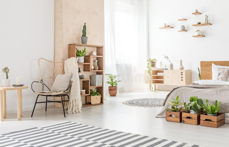 在木桌和地毯旁边的扶手椅子在与植物的卧室内部在床前面 实际照片 免版税图库摄影