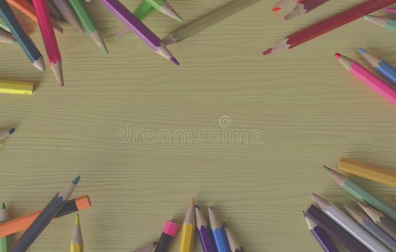 在木桌和木蜡笔上的背景 在棕色木地板上的多支色的铅笔 疏散的多支颜色铅笔  库存照片