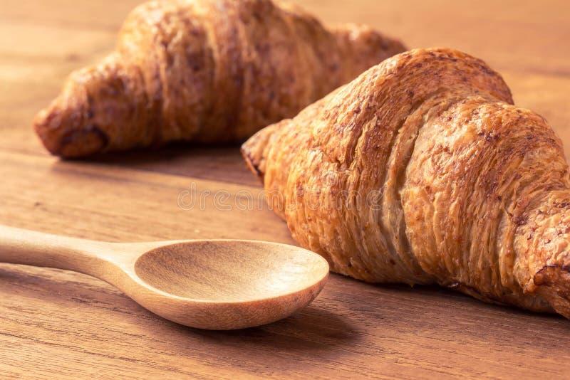 在木桌和木头匙子的新月形面包有过滤器作用的 免版税库存图片