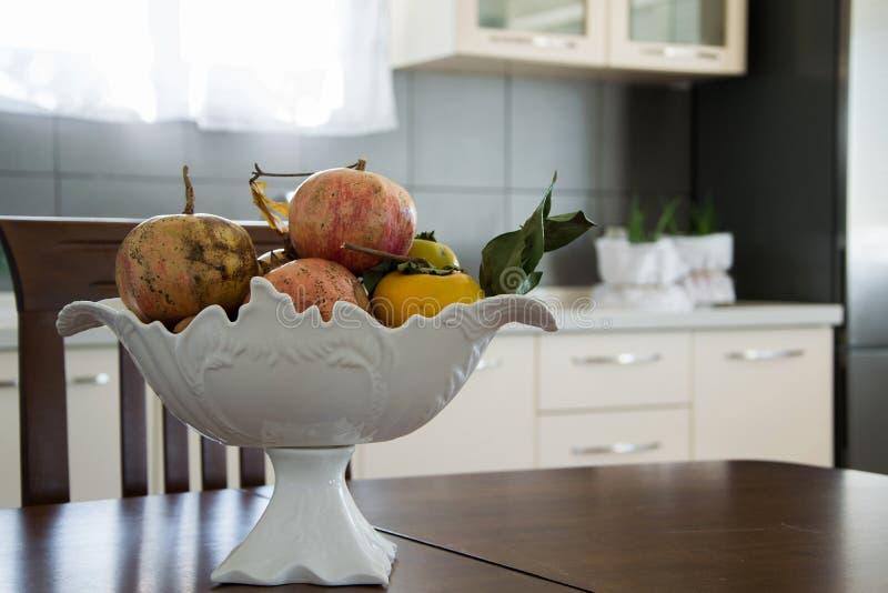 在木桌和现代厨房内部上的典雅的水果钵 免版税库存照片