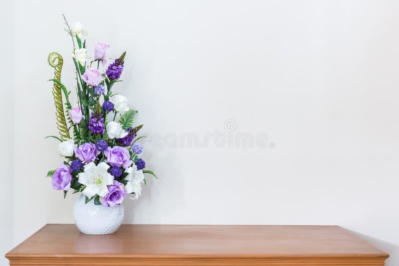 在木桌和白色墙壁上的人造花花瓶 库存照片