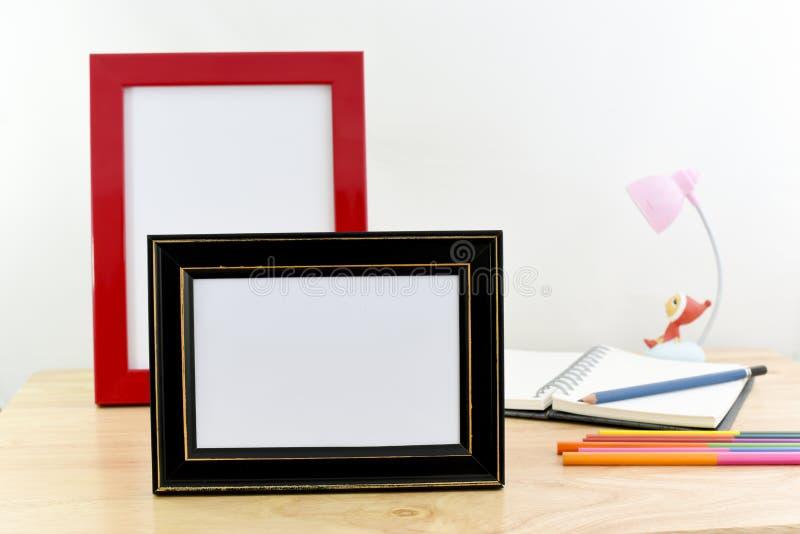 在木桌和白色背景上的空白的照片框架 免版税图库摄影