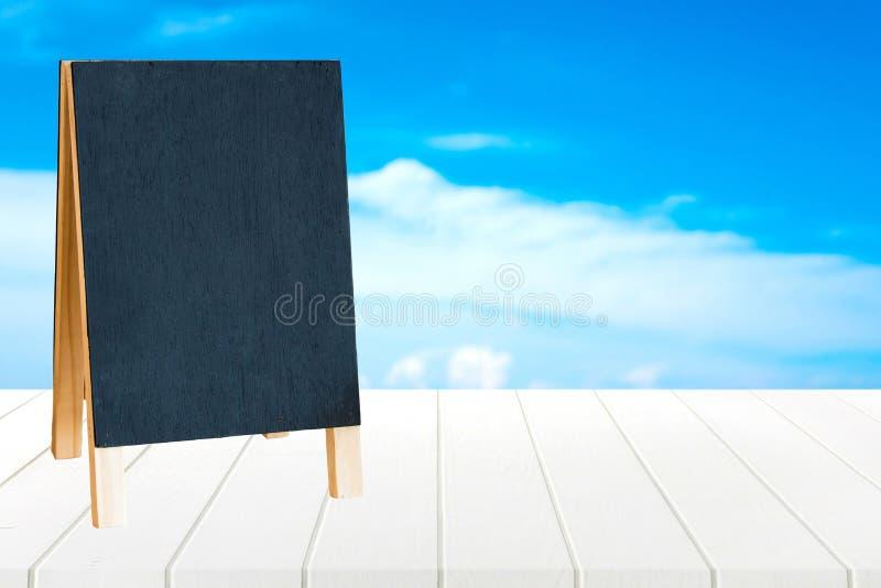 在木桌和蓝天背景的黑板 图库摄影