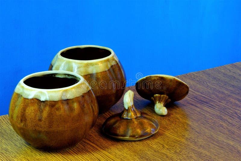 在木桌和蓝色背景上的泥罐 泥罐-有宽喉头的圆的陶瓷厨房船,烹调的在烤箱 免版税库存照片