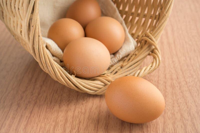 在木桌和鸡蛋上的一个鸡蛋在柳条筐 免版税库存照片