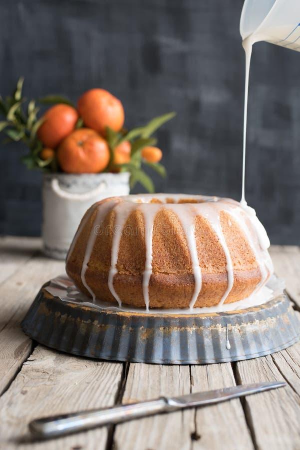 在木桌和黑暗的背景上的橙色蛋糕 免版税库存照片