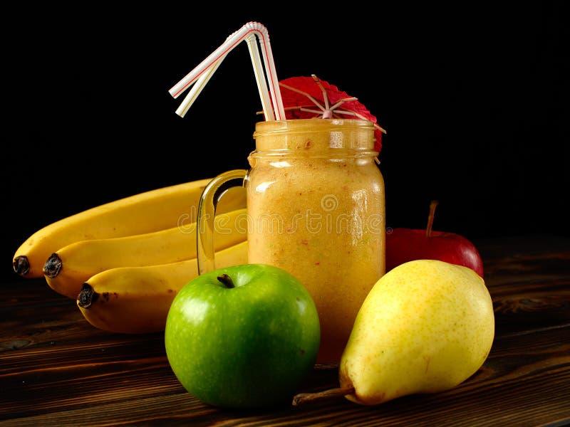 在木桌和黑背景上的水果的圆滑的人 库存图片