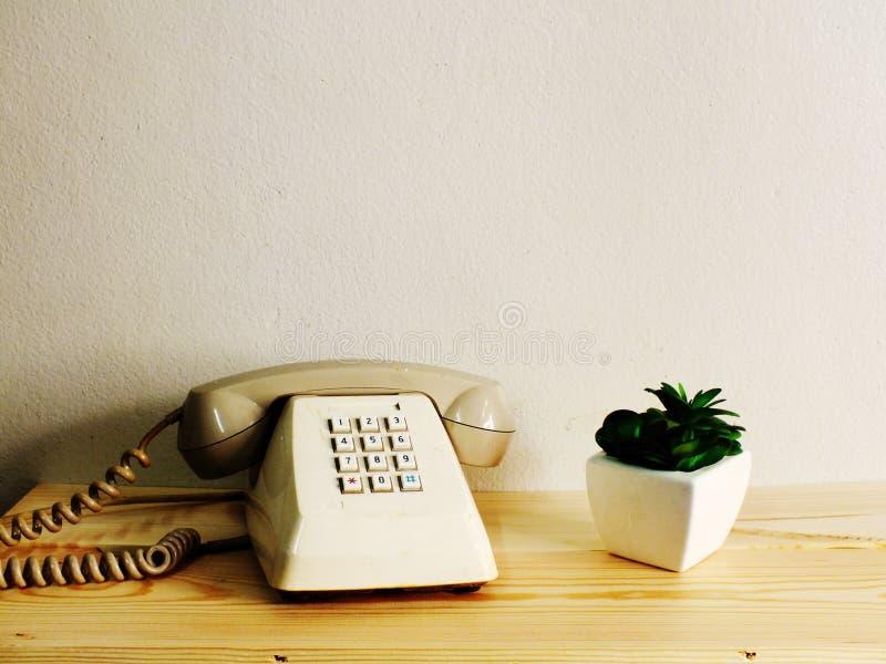 在木桌墙壁背景的减速火箭的电话 免版税库存图片
