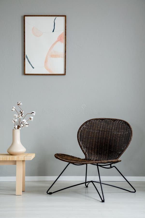在木桌旁边的现代扶手椅子与在灰色内部的花与在墙壁上的海报 免版税库存图片