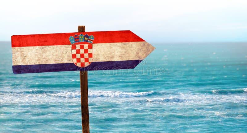 在木桌标志的克罗地亚旗子在海滩背景 有海滩和海和天空蔚蓝清楚的水  库存图片