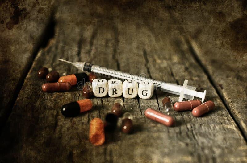 在木桌概念上瘾者的老破旧的污浊的照片药物药片 免版税库存图片