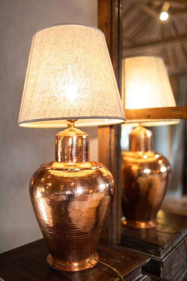 在木桌的古铜色灯 库存照片