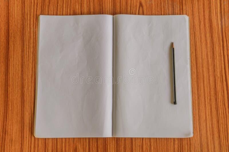 在木桌硬木地板上和铅笔隔绝的笔记本 准备为学生写笔记、报告、消息或者信, 图库摄影