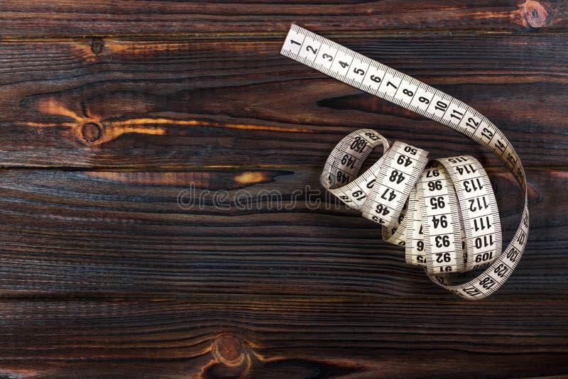 在木桌背景的关闭裁缝测量的磁带 白色测量的磁带浅dept领域 库存照片