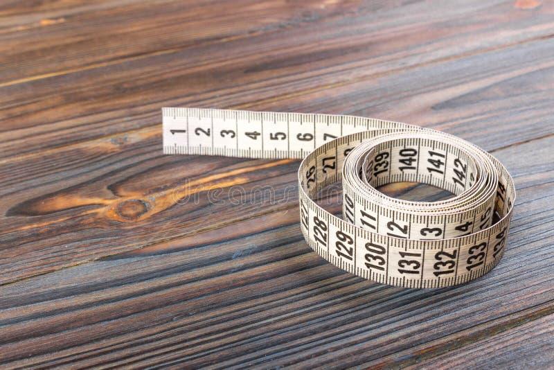 在木桌背景的关闭裁缝测量的磁带 白色测量的磁带浅dept领域 图库摄影