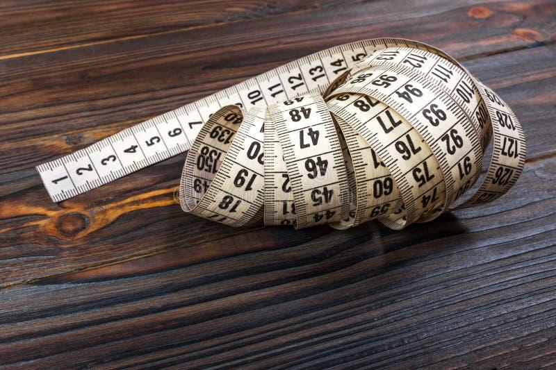 在木桌背景的关闭裁缝测量的磁带 白色测量的磁带浅dept领域 免版税库存照片