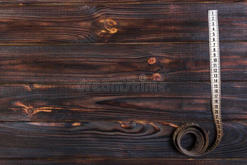 在木桌背景的关闭裁缝测量的磁带 白色测量的磁带浅dept领域 库存图片