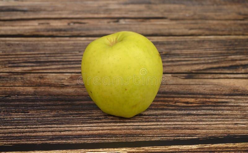 在木桌背景的成熟绿色苹果计算机 图库摄影
