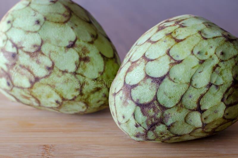 在木桌背景的毛叶番荔枝果子 两个毛叶番荔枝 clos 免版税库存照片