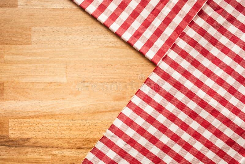 在木桌背景的红色方格的织品 对装饰 免版税图库摄影