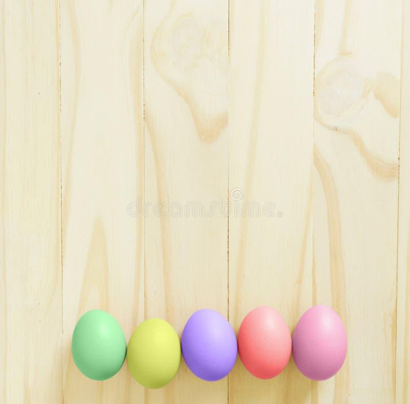 在木桌背景的葡萄酒五颜六色的复活节彩蛋 库存照片