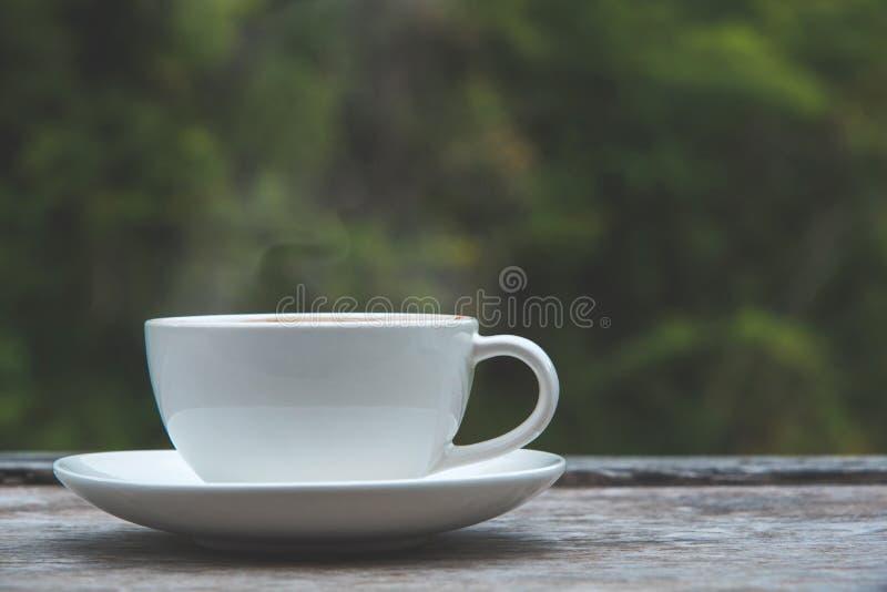 在木桌自然的咖啡杯弄脏了背景 库存照片