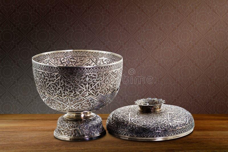 在木桌面的泰国古色古香的古老难看的东西银碗在葡萄酒褐色紫色混凝土墙背景 库存照片