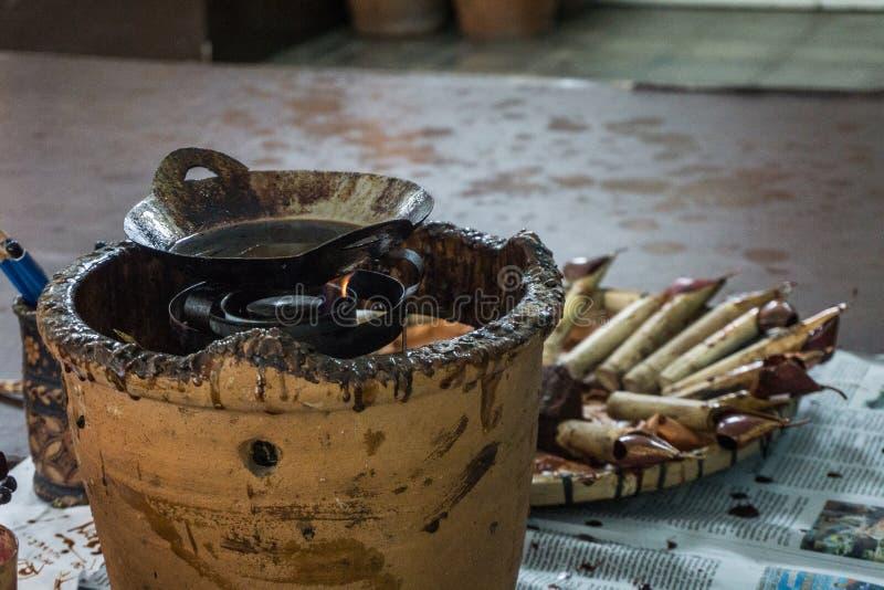 在木桌顶部的倾斜的和热的蜡处理照片的蜡染布的拍在北加浪岸印度尼西亚 免版税图库摄影