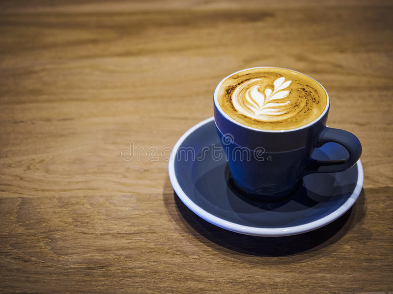 在木桌餐馆商店咖啡馆的咖啡杯热奶咖啡 免版税库存照片