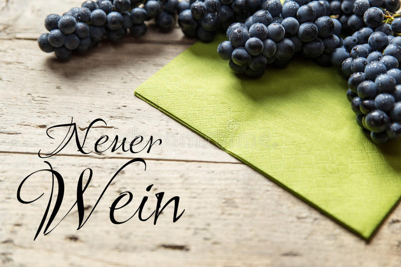 在木桌,德国文本,概念federweisser上的蓝色葡萄 免版税库存图片