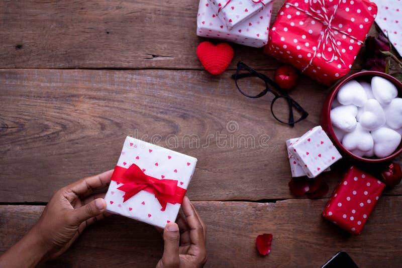 在木桌,情人节庆祝背景上的人的手举行礼物盒 库存照片