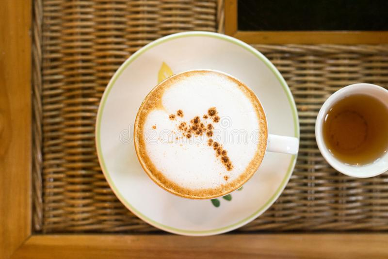 在木桌,拿铁艺术被定调子的葡萄酒颜色,与拷贝空间的顶视图上的咖啡杯文本的 免版税库存图片
