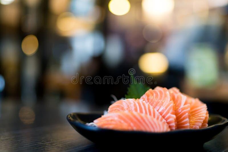 在木桌,日本食物可口菜单, bokeh上的切的三文鱼生鱼片弄脏了与拷贝空间的背景 库存图片