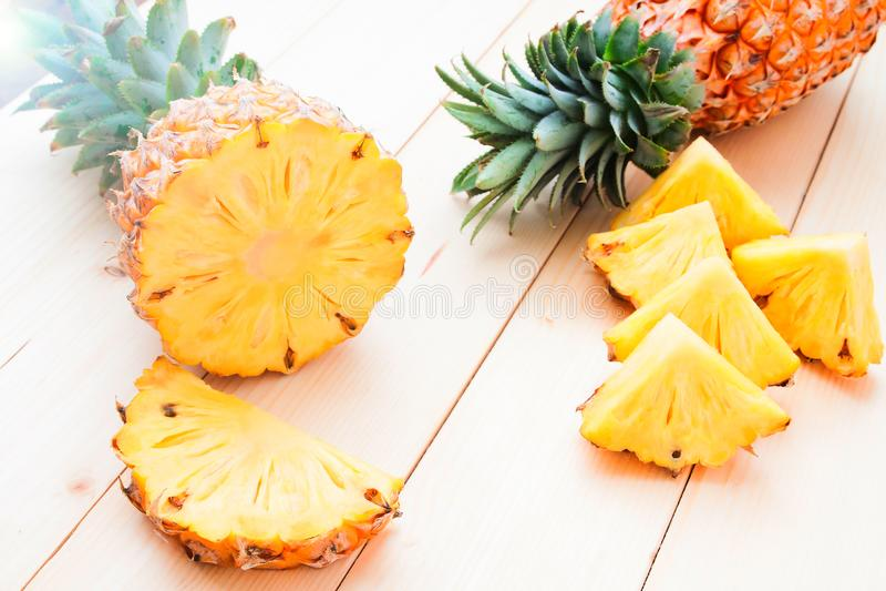 在木桌,热带水果上的新鲜的整个和被切的菠萝 库存照片