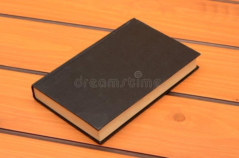 在木桌,研究题材上的黑名册大模型 免版税图库摄影