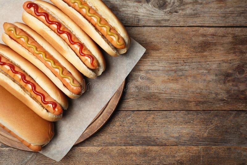 在木桌,顶视图上的鲜美新鲜的热狗 免版税库存照片