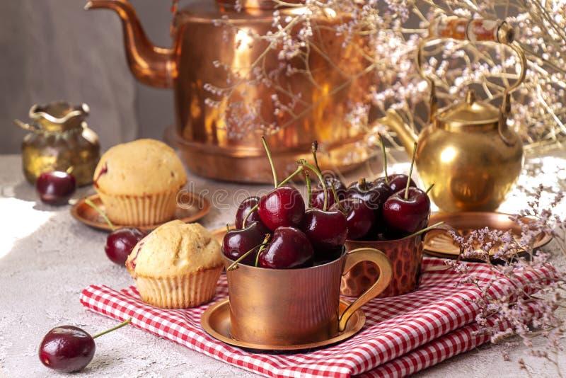 在木桶匠杯子和松饼的甜樱桃反对与老木桶匠茶壶的背景 r 免版税库存照片