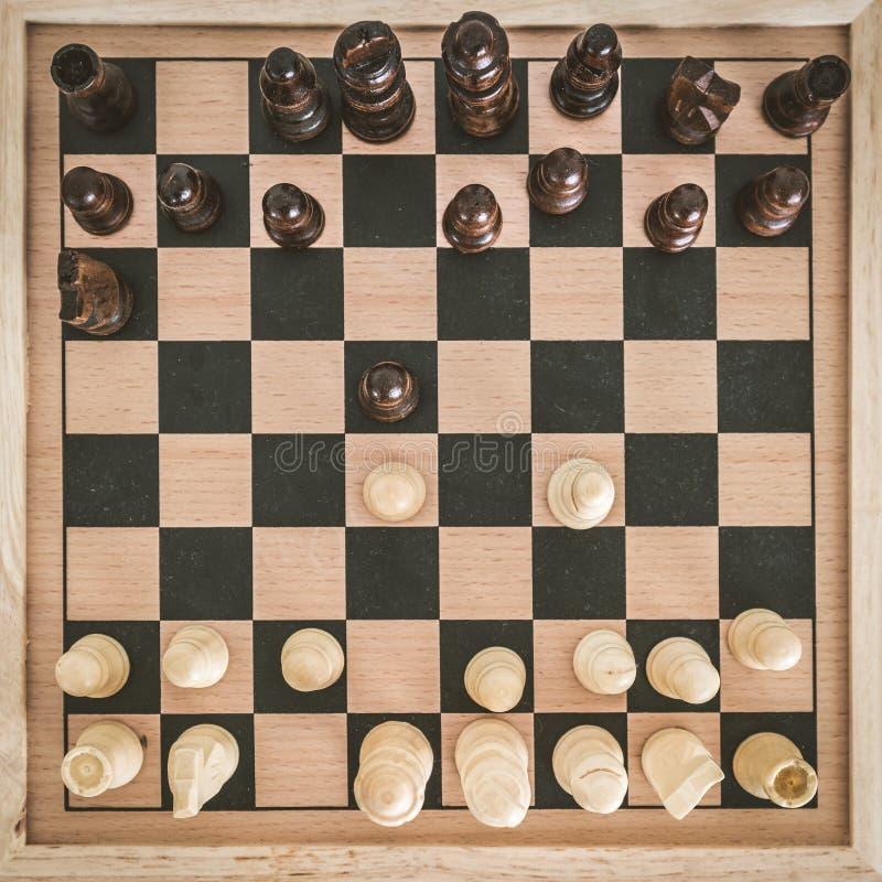 在木棋盘的顶视图有棋形象的准备好比赛和man';做象棋移动的s手在白色木桌 免版税库存照片