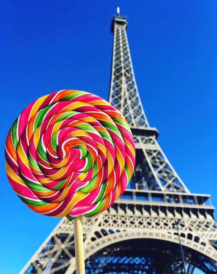 在木棍子的五颜六色的彩虹棒棒糖漩涡在埃菲尔铁塔背景 免版税库存图片