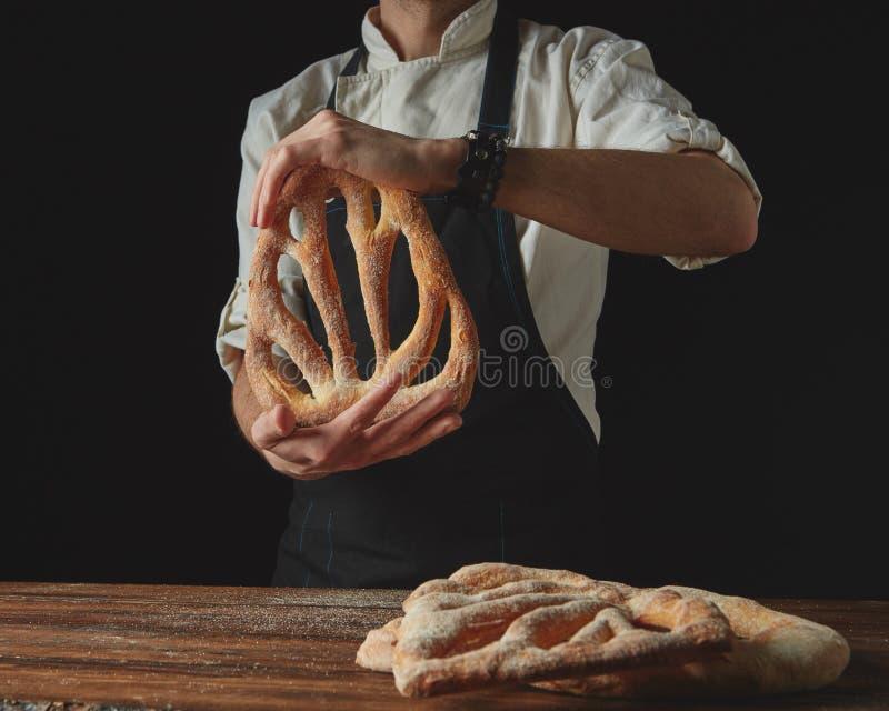 在木棕色桌背景,人` s手举行面包fougas 库存照片