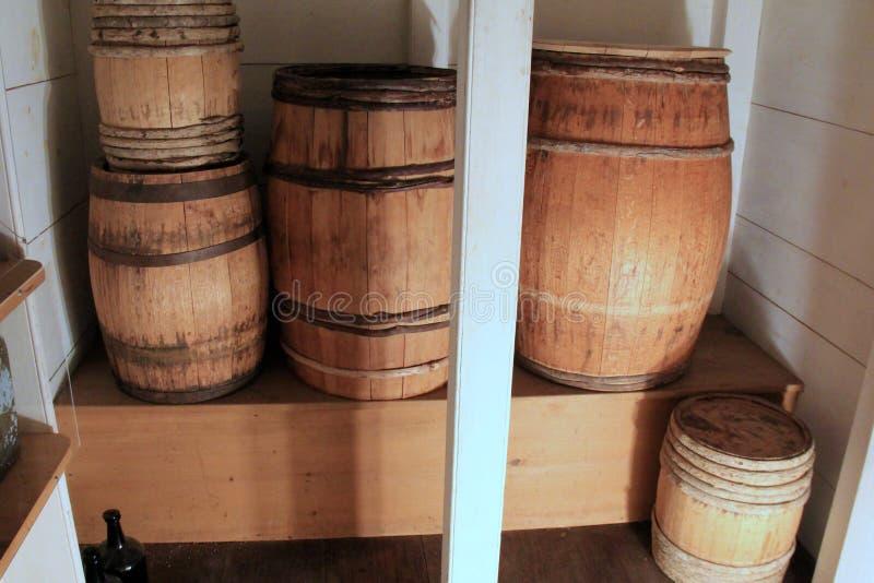 在木棚架的壁橱设置的老被风化的葡萄酒桶 库存照片