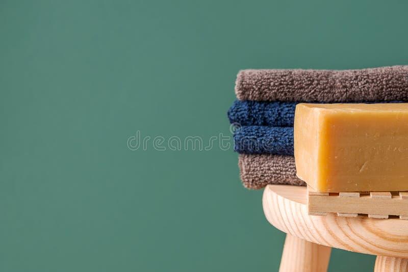 在木椅子的被折叠的棉花特里毛巾洗碗布手工制造工匠橄榄油肥皂在绿色墙壁背景的卫生间里 ?? 图库摄影